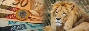 Leão símbolo do Imposto de Renda em primeiro plano e notas de dinheiro e moedas ao fundo